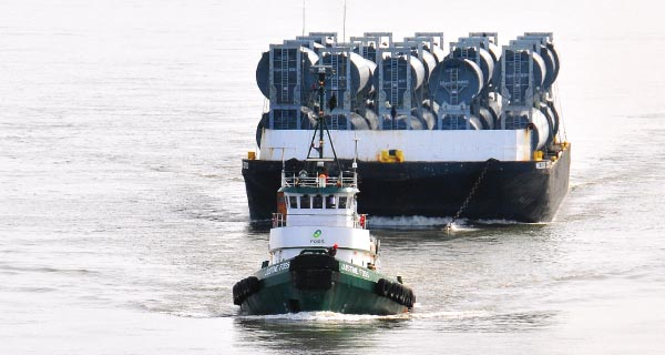 Custom-designed barges transported 10 sets of wind tower components at once.