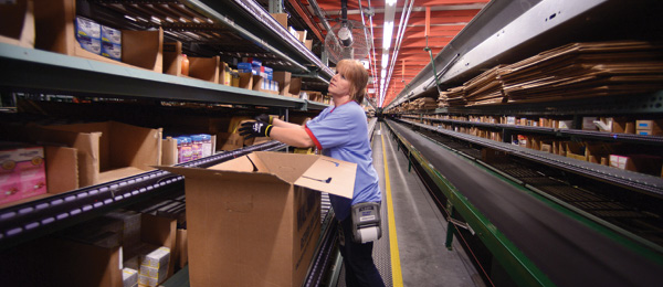 A Walmart associate stocks inventory on warehouse shelves
