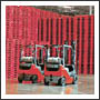 Forklifts in front of a huge stack of pallets