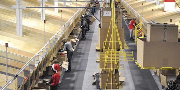 Workers pull packages off DSW's sortation system